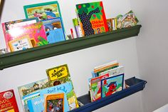 painted rain gutters for displaying children's books - SO clever.