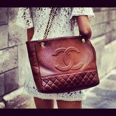 A brown rust color tote chanel bag. With gold chain handles. Large signature chanel embroidered on the tote