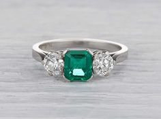 Antique Art Deco ring made in platinum and centered with an approximate .80 carat emerald cut emerald. Accented with two old European cut diamonds weighing approximately one carat total. Circa 1925.