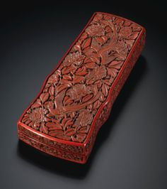 A Cinnabar Lacquer Qin-Shaped Writing Box.