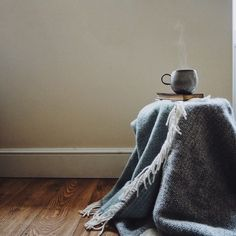 Steaming tea cup on a pile of books and a blanket against a pale wall