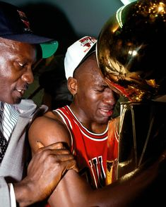 Iconic NBA Photos - Andrew D. Bernstein-Michael Jordan sobbing into the trophy after his first title, his father at his side.