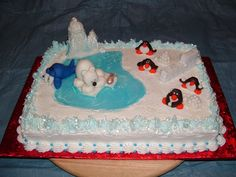 "Winterland fun! - White cake with strawberry filling.  Decorated with decorator icing, and royal icing.  Penguins, Polar bear, and Walrus are fondant.  Block ice wall made with sugar cubes.  Piping gel used for water and ""chilly"" ice accents!!  Notice the humor incorporated into this wintery scene!"
