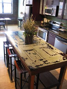 I really want this look for my kitchen table. Using an old Door as a table. Genius.