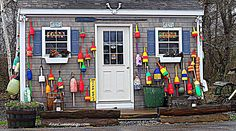 Love the colors in the buoys on this little fish shack!    www.NHCoastalLiving.com