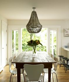Bella Mancini Design - Gorgeous cottage dining room design with rustic farmhouse dining table, modern white plastic dining chairs, gray abalone shells Oly Studio Jenny Chandelier and French doors.