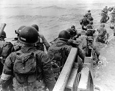 Un groupe de Medics débarquent sur la plage d'Utah Beach à partir d'un LCM. A leur descente, les soldats ont de l'eau jusqu'à la taille.