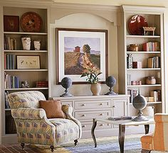 Love the look of this.  Built-ins, center cabinet with cut out above (for TV, instead of painting).  The cabinet is then used for media storage.