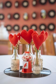 Centros de mesa com discos de vinil, garrafinhas, baleiros e corações de feltro no casamento da Letícia e do Clauber com o tema rockabilly em São Paulo, onde o casal fez a própria decoração.
