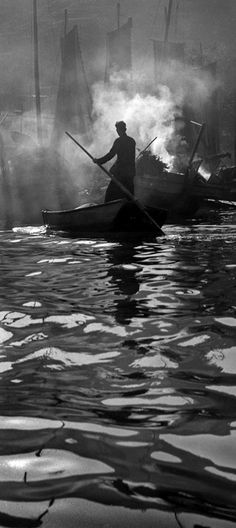 Stunning Black and White image of a fisherman with his boat. I am not sure where or when this was taken, but I absolutely love the reflections on the water, with the silhouette of the fisherman and the smoke in the background.
