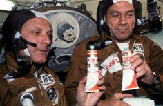 Astronauts Thomas Stafford (left) and Donald Slayton hold containers of Soviet space food in the Soyuz Orbital Module during the joint U.S.-USSR Apollo-Soyuz Test Project in 1975. The containers hold borsch (with a vodka labels stuck over the top). - Gourmet Astronauts: Favorite Space Food