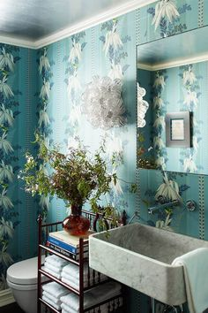An antique floral wallpaper design makes a statement in the bathroom of designer Katie Ridder's townhome. The sink is custom-made and is flanked by antique sconces. #wallpaper #wallpaperbathroom #bestwallpaper