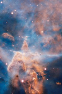 Mystic Mountain This craggy fantasy mountaintop enshrouded by wispy clouds looks like a bizarre landscape. But it is indeed a pillar of gas and dust, three light-years tall, which is being eaten away by the brilliant light from nearby bright stars....