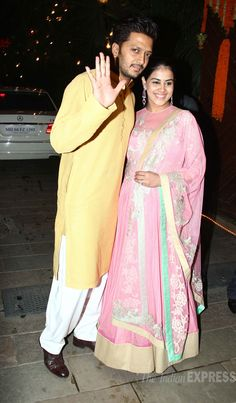 Riteish Deshmukh gives us a wave, while mom-to-be Genelia D'Souza glowed in a pink creation, proudly showing off her baby bump at Amitabh Bachchan's Diwali bash. #Bollywood #Fashion #Style #Beauty