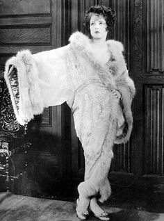 """""""Clara Bow wears a wrap-like negligee made of Elizabeth crepe, embroidered with silver sequins. The satin ribbon lining contrasts luxuriously with the marabou trimming"""". 1927"""