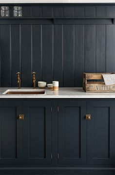 From deVOL kitchens in the UK, a gorgeous bank of cupboards painted in 'Pantry Blue' with Carrara marble worktops and an under-mounted copper sink.