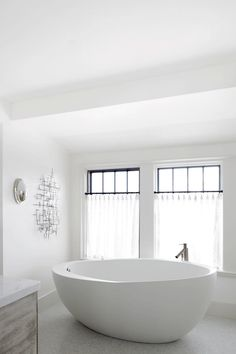 Modern bathroom features crisp white walls framing steel windows dressed in white sheer cafe curtains over a modern egg shape tub paired with an off set modern tub filler atop mosaic marble floor.