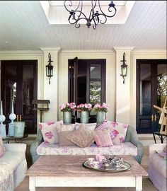 this is the front porch & it is lovely from the wood ceiling, light fixtures & molding to the soft places to sit w/sweet fabrics in pinks to the adorable galvanized buckets of pink flowers....