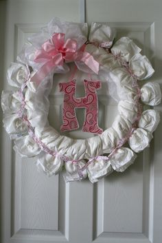 What a great decoration/gift for a baby shower/Mom-To-Be. Start with a wire wreath frame from your local craft store. Use festive colored ribbons and tie diapers on so the opening is on the outside...