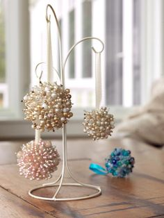 "Make Christmas Ornaments From Old Necklaces: For this glitzy project, you will need a hot-glue gun and glue sticks, scissors, small Styrofoam balls, a box of 1-1/16"" dressmaker pins, 2 to 4 old costume jewelry necklaces (depends on the number and size of ornaments, package of clear seed (bugle) beads and ribbon. From DIYnetwork.com"