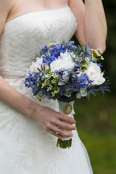 Bridal bouquet - white/ivory peonies, blue delphinium, wax flowers, blue thistle, and hypericum berries.