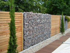 Gabion Wall Stone and Wood Fence. Along the fence line Gabion Stone, Gabion Retaining Wall, Stone Fence, Wood Stone, Backyard Fences, Fenced In Yard, Garden Fencing, Mesh Fencing, Garden Trellis