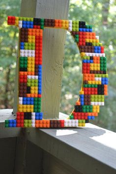 This is a 9 1/2 inch wooden D that is painted yellow and covered in multiple colors of Legos. This would be a perfect addition to a lego