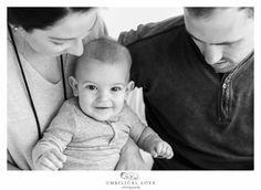 baby looking at camera while mum and dad look at him