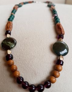 This necklace looks like it was pulled out of the forest with its earthy colours, natural agate stone and wood beads! A beautiful and unique design, perfect for any nature lover or your hippie/bohemian style. This necklace is made with -Natural Agate Coins - Wood Beads - Glass Beads - Czech Fire Polished Glass Beads The necklace is a medium size measuring at approx. 20 inches Items come in a organza pouch. Check out more of my beaded necklace designs here…