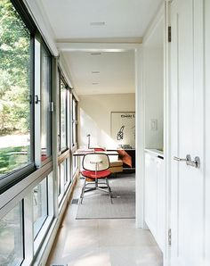 Modern guesthouse renovation in New York hallway and kitchenette and the back of a vintage seventies #Eames molded plastic chair