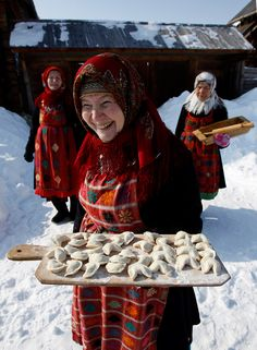 """Members of the singing group """"Buranovskiye Babushki"""" offer home-made dumplings at the Folk Museum near the village of Ludorvai in the central Russian region of Udmurtia March 16, 2012. A group of ladies ranging in age from 42 to 86 who sing traditional songs and pop classics in their own language, they have been voted by popular demand to represent Russia in the forthcoming Eurovision song contest."""