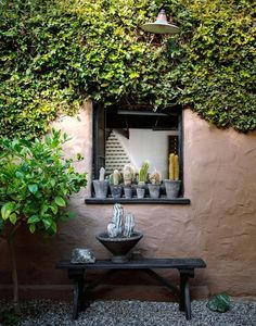 A Spanish-Style Compound for Indoor-Outdoor Living in L.A.: Pots of cactus stand on a window's ledge of a Southwestern-inspired home.