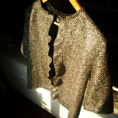 Giacchetta a manica corta realizzata in lana e lame' color argento e con frappa sull apertura davanti.Short sleeved jacket made of wool and blades ' silver and frappa opening on the front.