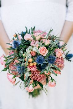 A wild bouquet filled with blue thistle, spray roses, and topped off with vintage tinted carnations
