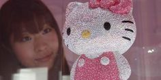 Hello Kitty: A woman looks at a Hello Kitty figurine.