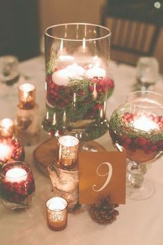 a cozy traditional Christmas wedding centerpiece of pinecones, mercury glass candle holders and jars with evergreens, cranberries and candles wedding centerpieces Christmas Wedding Centerpieces, Red Centerpieces, Christmas Wedding Decorations, Wedding Table Centerpieces, Cranberry Centerpiece, Centerpiece Ideas, Christmas Wedding Flowers, December Wedding Colors, Decoration Table