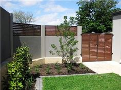 Mixed material fencing: solid gray and stained wood slats