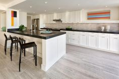 The vertical lines in this contemporary kitchen are emphasized by clean, colorful modern artwork. Shaker-style cabinets maximize storage and blend with the white walls, allowing the artwork to pop. Quartz countertops are low-maintenance and feature a thick profile that gives the space an industrial touch.