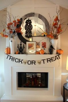 Halloween mantle.  I could easily do something similar in the foyer.  Love the use of the photos in black and white frames.