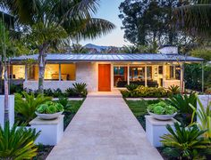 gorgeous house with metal roof, large porch and tropical landscaping
