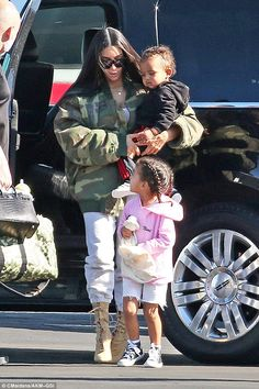 Staying close: North looked adorable in her bright pink hoodie - which featured her name stitched on the front