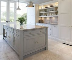 White & gray kitchen design with white kitchen cabinets, gray chunky kitchen island, granite counter tops & backsplash, open shelves with beadboard, French doors and polished nickel fan pendants.