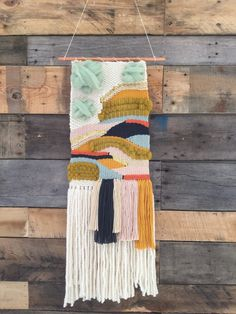 Handmade woven wall art in ivory, charcoal, light blue, red-orange, blush, cream, mustard yellow, chartreuse and seafoam roving, and bits of gold