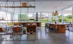 Living comedor integrado moderno y luminoso en una casa en Nordelta. Decoración en madera, cuero y acero, con piso de cemento alisado.