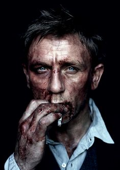 Daniel Craig by Jean Baptiste Mondino. Blue eyes peering from his bloody face.. wish there was smoke in this photo..