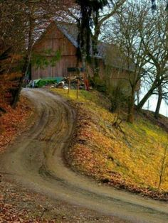 .Barn on a hill, winding country road, late fall.