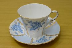 Royal Standard Fine Bone China Margaret Rose Blue Paneled Cup and Saucer England. This is a beautiful English fine porcelain teacup and saucer by Royal Standard. The pattern is Margaret Rose. It is fine bone china and the set is a standard teacup size with a 5 15/16 saucer. It has lovely
