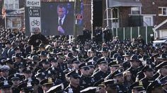 Law enforcement officers turn their backs on a live video monitor showing New York City Mayor .