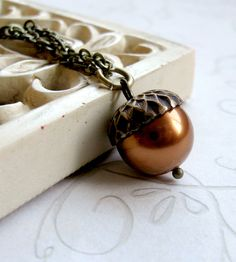 Copper Swarovski Acorn Necklace by Botanical Bird on Scoutmob -- This sweet little acorn necklace features one high-quality, copper-colored Swarovski glass pearl along with a solid brass acorn bead cap. The necklace comes on a brass chain, with a solid brass clasp closure.  -- $22 -- saved 9-21-16