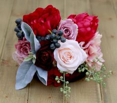 This bouquet is filled with some of everyone's favorite flowers in rich colors. Featured is the Medium/Regular size Bouquet. Includes: - Pink Dahlia - Blush Roses - Plum Burgundy Ranunculus - Fuchsia